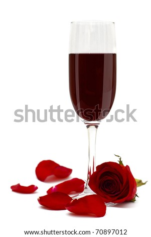 Glass of red wine and rose flower and petals