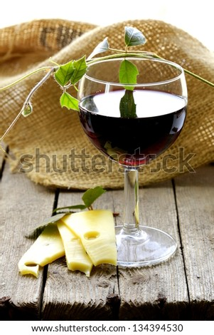 glass of red wine and slices of cheese on a wooden table