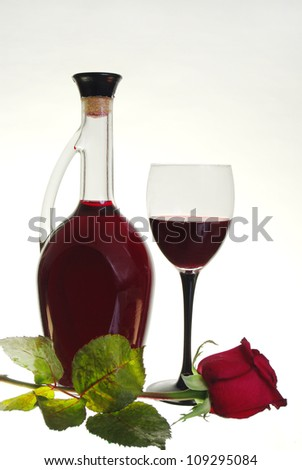 Glass of red wine,  bottle of wine and red rose. White background.