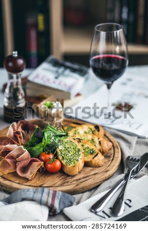 Glass of red wine, cheese and prosciutto, old wooden barrel #285724169