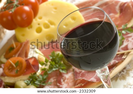 glass of red wine close up with food in background
