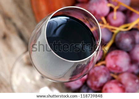 Glass of red wine closeup and purple grapes on rustic wood background.Alcohol,wine making.