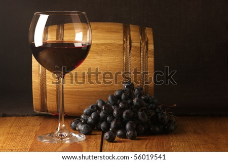 Glass of red wine, dark grape and souvenir barrel on wooden surface. - stock photo