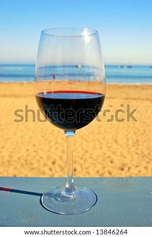 Glass of red wine on a restaurant's deck railing by the ocean beach