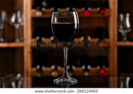 Glass of red wine on bar background #288124409