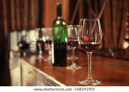 Glass of red wine on bar counter #548241901