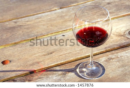 Glass of red wine on old rustic table