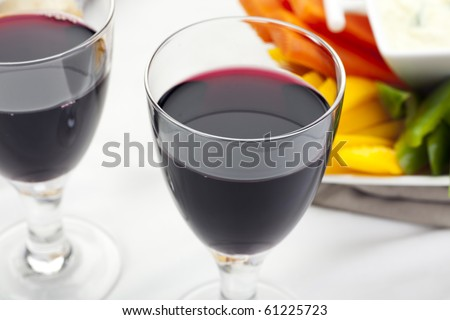 Glass of red wine on table with appetizers in background.