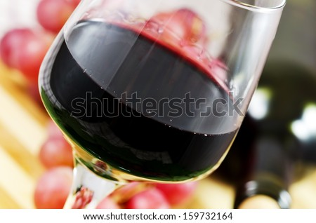 Glass of red wine with bottle and grapes in the background.