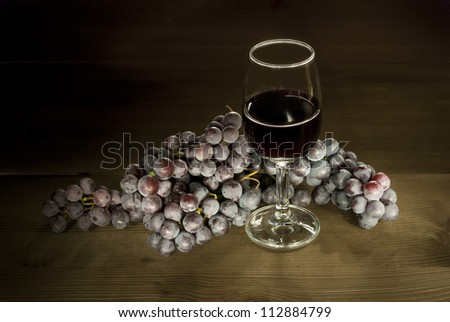 glass of red wine with clusters of grapes on wooden table