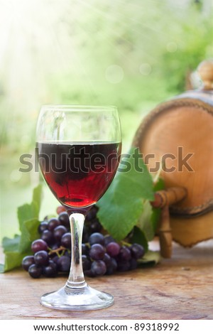 Glass of red wine with fresh harvested grapes and wine barrel