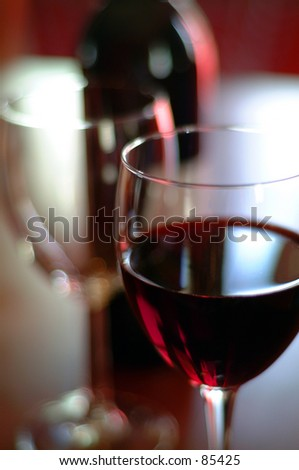 Glass of red wine with glass and bottle in background