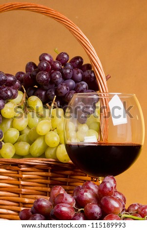 Glass of red wine with grapes and a basket.
