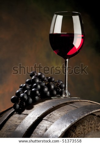glass of red wine with grapes and old barrel