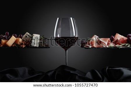 Glass of red wine with various cheeses , fruits and prosciutto on a black background.