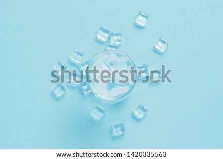 Glass of refreshing cold water with ice and ice cubes on a blue background. Concept of thirst, heat, refreshment in the summer. Flat lay, top view #1420335563