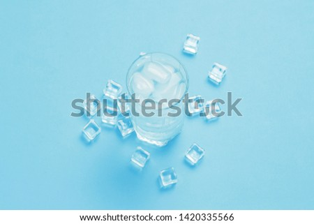 Glass of refreshing cold water with ice and ice cubes on a blue background. Concept of thirst, heat, refreshment in the summer. Flat lay, top view #1420335566