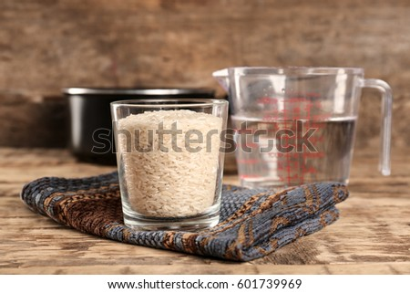 Glass of rice and measuring jug with water on wooden table Stock fotó ©