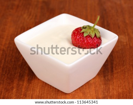 Glass of ripe strawberries with cream on wooden background