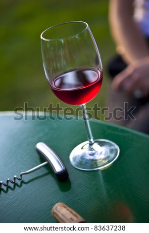 Glass of rose wine, cork and corkscrew on a table