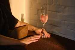 Glass of rose wine in the hands of a girl in the rays of the setting sun at home. Tasting of alcoholic beverages. Celebrate and enjoy the moment. Romantic evening aperitif. Close-up glass of wine