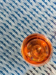 Glass of rose wine viewed from above on the glass table top of garden furniture