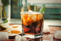 Glass of rum on the wooden background, Cuba Libre or long island iced tea cocktail with strong drinks, cola,