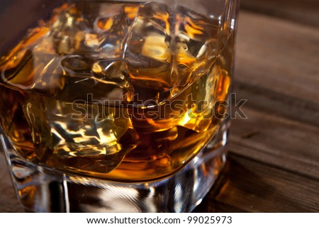 Glass of scotch whiskey and ice on a wooden table