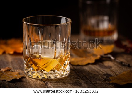 Glass of scotch whiskey and ice on wooden background with autumn leaves ストックフォト ©