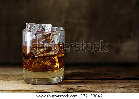 glass of scotch whiskey with ice cubes on a rustic wooden table, copy space in the brown background Foto stock ©