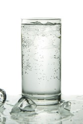 Glass of soda water with ice on isolated white background