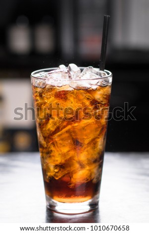 Glass of soft drink with ice, vertical shot, dark background