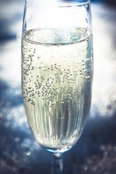 Glass of sparkling cold champagne with bubbles on shining snow with back light