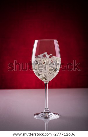 Glass of sparkling wine over ice cubes; preparing wine-based long drink