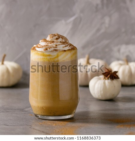 Glass of spicy pumpkin latte with whipped cream and cinnamon standing on gray kitchen table with coffeepot and decorative white pumpkins. Coffee beans and spices above. Square image - Shutterstock ID 1168836373