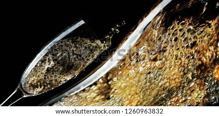 Photo of Glass of splashing champagne on black background. Holiday concept image, free space for your content.