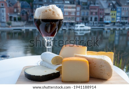 Glass of strong Belgian abbey beer and tasting of cheeses made with trappist beer and fine herbs with view on Maas river in Dinant, Wallonia, Belgium Foto stock ©