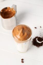 Glass of tasty dalgona coffee on table