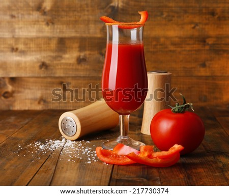 glass of tasty tomato juice and pepper on wooden table