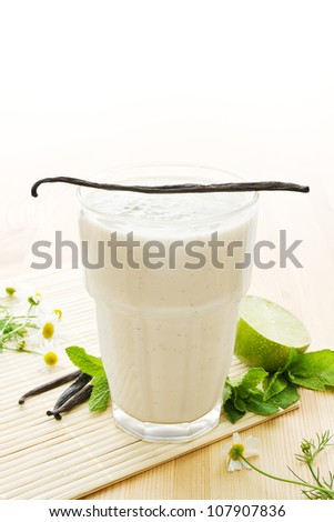 Glass of vanilla milkshake with vanilla beans, limes, mint leaves and daisy flowers on wood