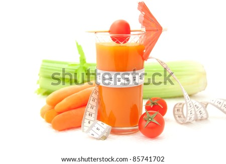 Glass of vegetable juice with tape measure and fresh vegetables on white background