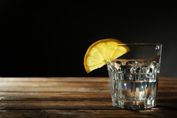 Glass of vodka with lemon and ice on dark background