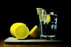 glass of water and lemon on black background