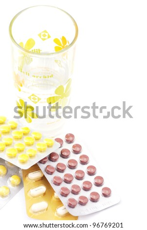 Glass of water and pills isolated on white