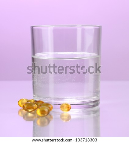 Glass of water and pills on purple background
