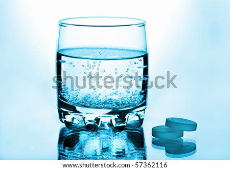 Glass of water and pills toned blue