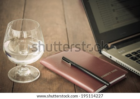 glass of water blown organizer or notebook and pen and the laptop