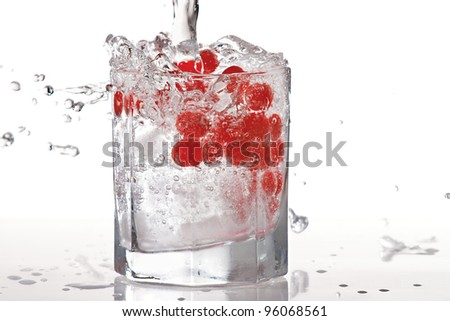 Glass of water, ice and red cranberries with splash on a white background - stock photo
