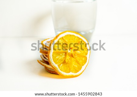 Glass of water isolated white background with dried lemon slice in the background. Close up shot #1455902843