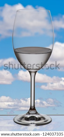 glass of water on glass base with fantasy cloud background